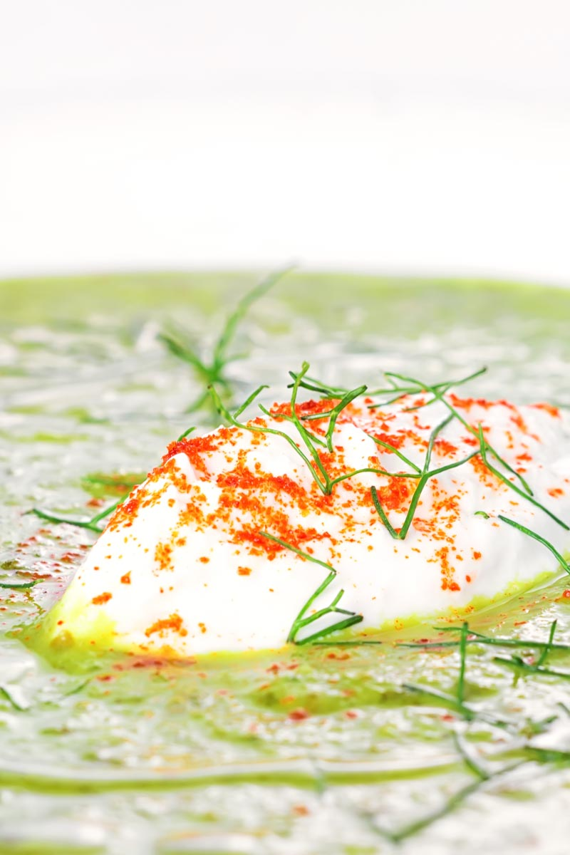 Portrait close up image of sorrel and fennel soup served in a white bowl with a dollop of sour cream and sprinkling of paprika