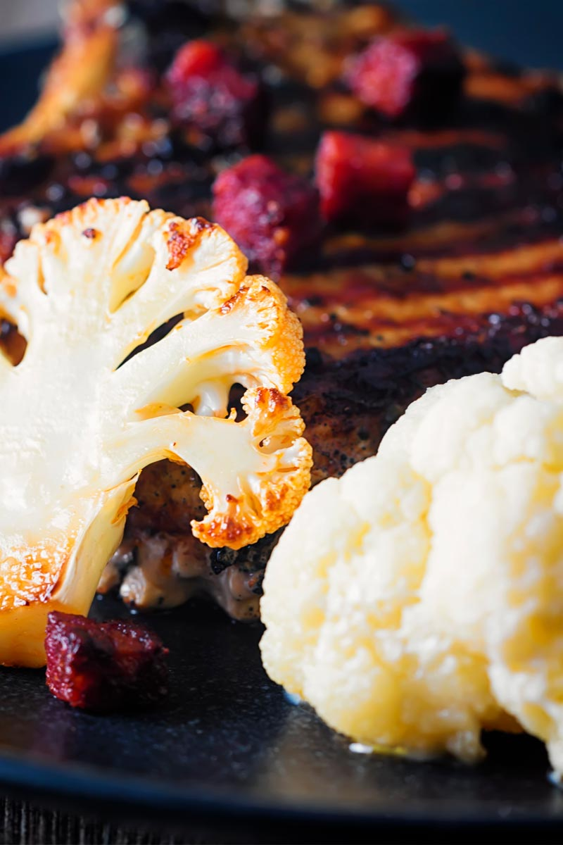 Close up portrait image of poached and fried cauliflower with chorizo sausage served on a black plate