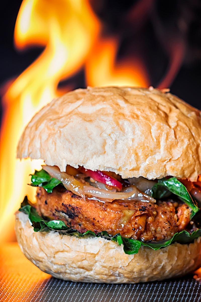Portrait image of a spicy bean burger topped with an onion and peach chutney served on a bun with a flaming background