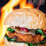 Portrait image of a spicy bean burger topped with an onion and peach chutney served on a burger bun with a flaming background with text
