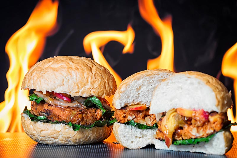 Landscape image of a spicy bean burger topped with an onion and peach chutney served on a burger bun with a flaming background