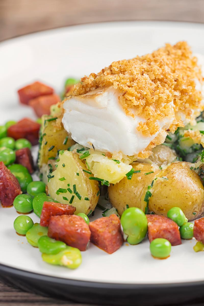 Portrait image of a baked cod fillet served on new potatoes served with peas, broad beans and chorizo sausage on a white plate