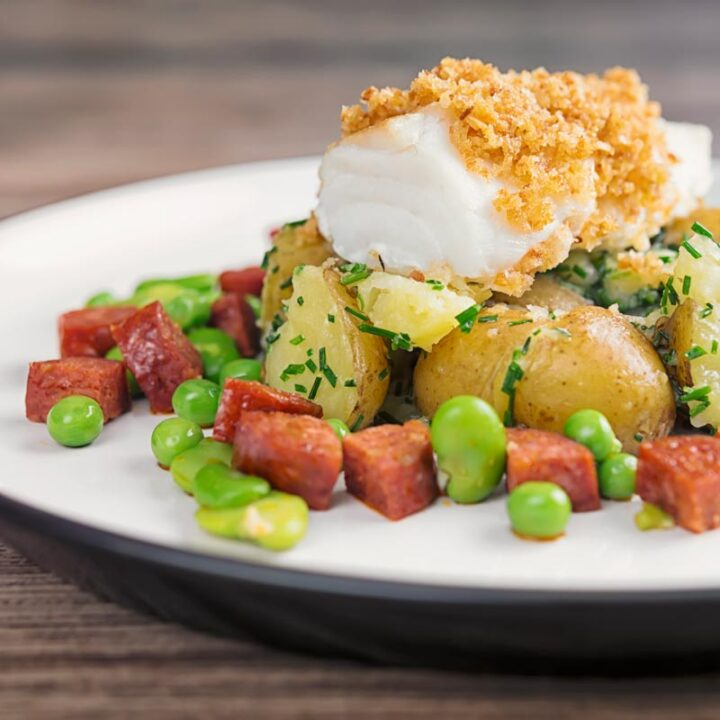 Square image of a baked cod fillet served on new potatoes served with peas, broad beans and chorizo sausage on a white plate