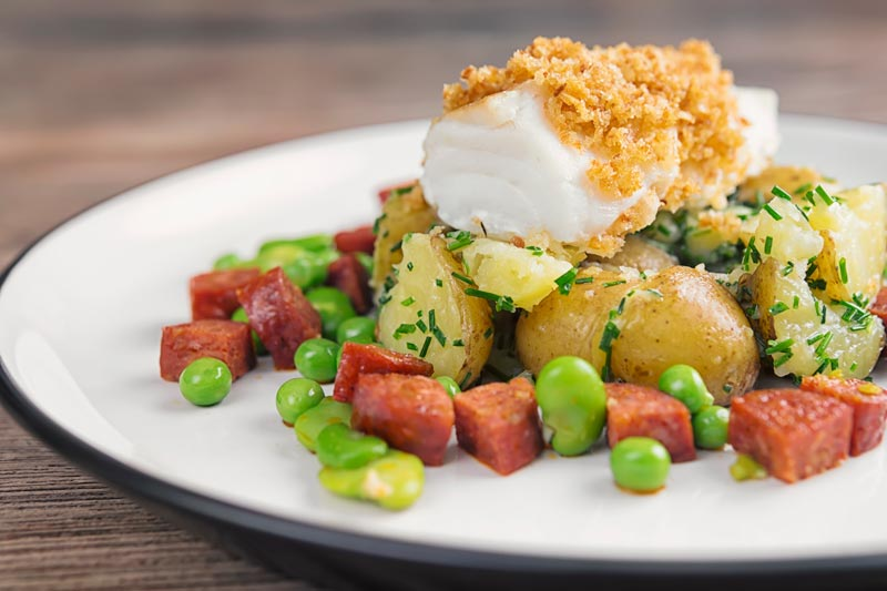 Landscape image of a baked cod fillet served on new potatoes served with peas, broad beans and chorizo sausage on a white plate