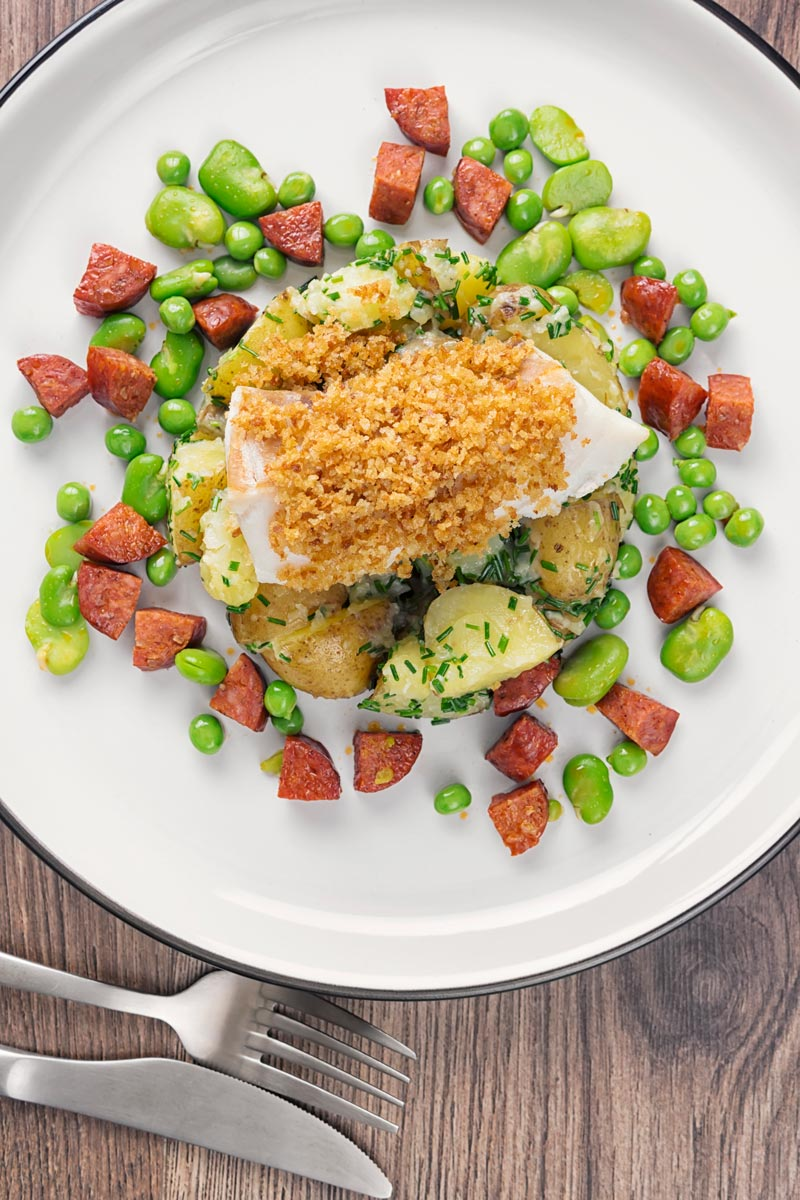 Portrait overhead image of a baked cod fillet served on new potatoes served with peas, broad beans and chorizo sausage on a white plate