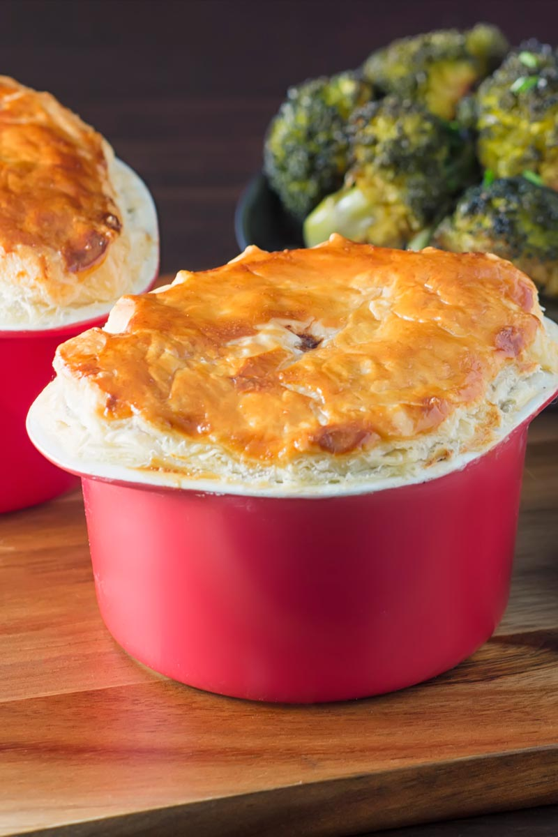 Portrait image of a beef and ale pie served pot pie style in a red pot