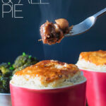 Portrait image of a beef and ale pie served pot pie style in a red pot with a fork removing steaming pie filling with text overlay