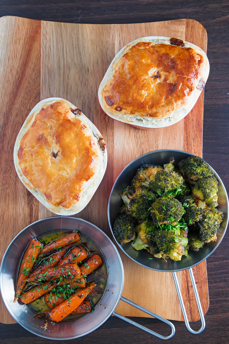 Portrait over head image of two beef and ale pies served pot pie style with glazed carrots and broccoli