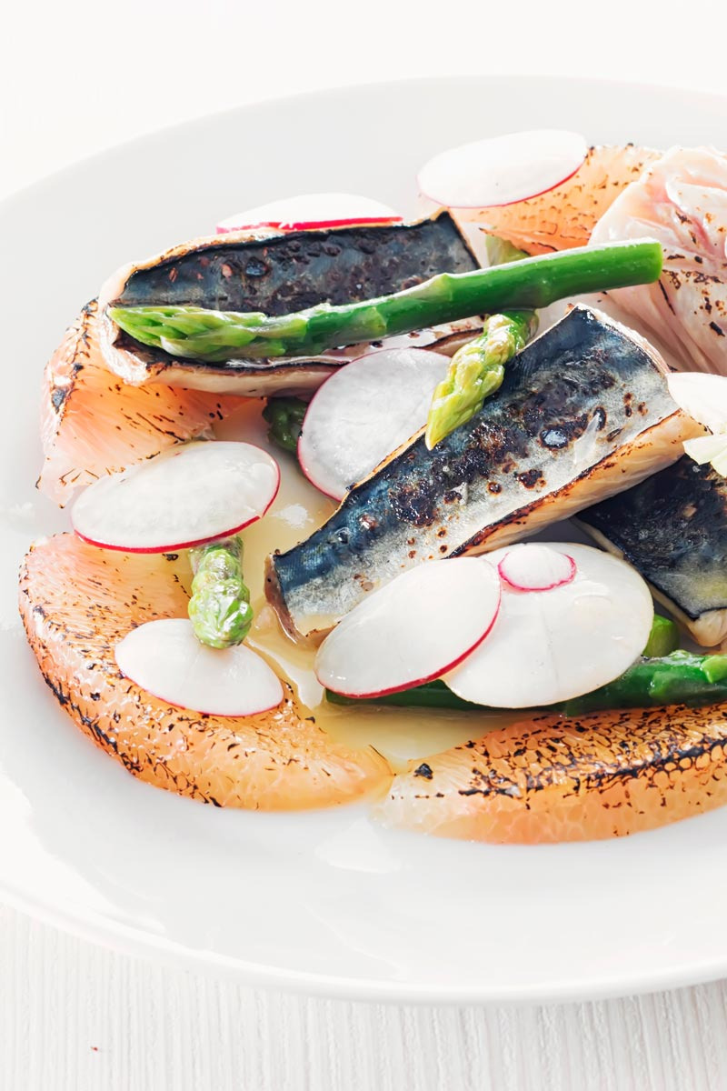 Portrait image of cured mackerel served in a salad featuring asparagus spears and pomelo