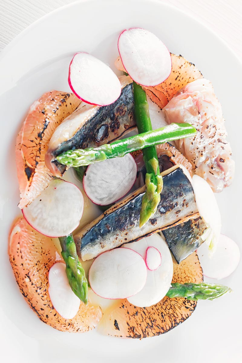 Portrait overhead image of cured mackerel served in a salad featuring asparagus spears and pomelo