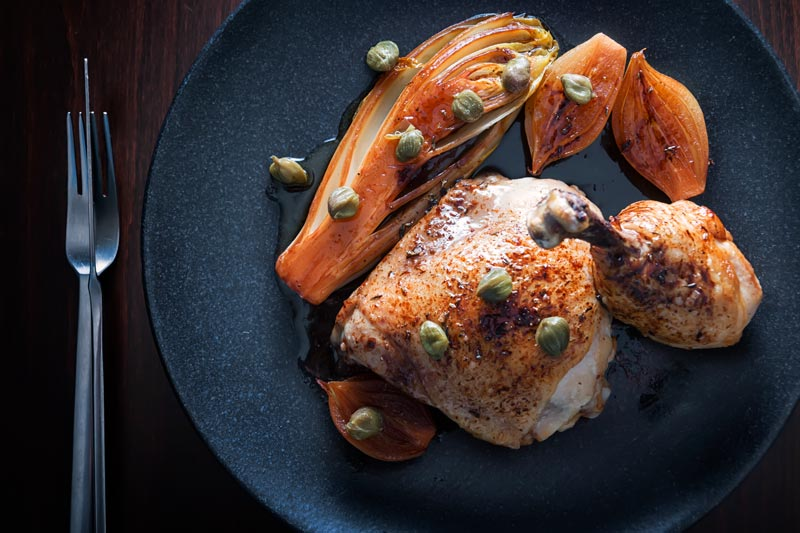 Landscape overhead image of braised chicken legs served with Belgian Endive, shallots and capers on a black plate