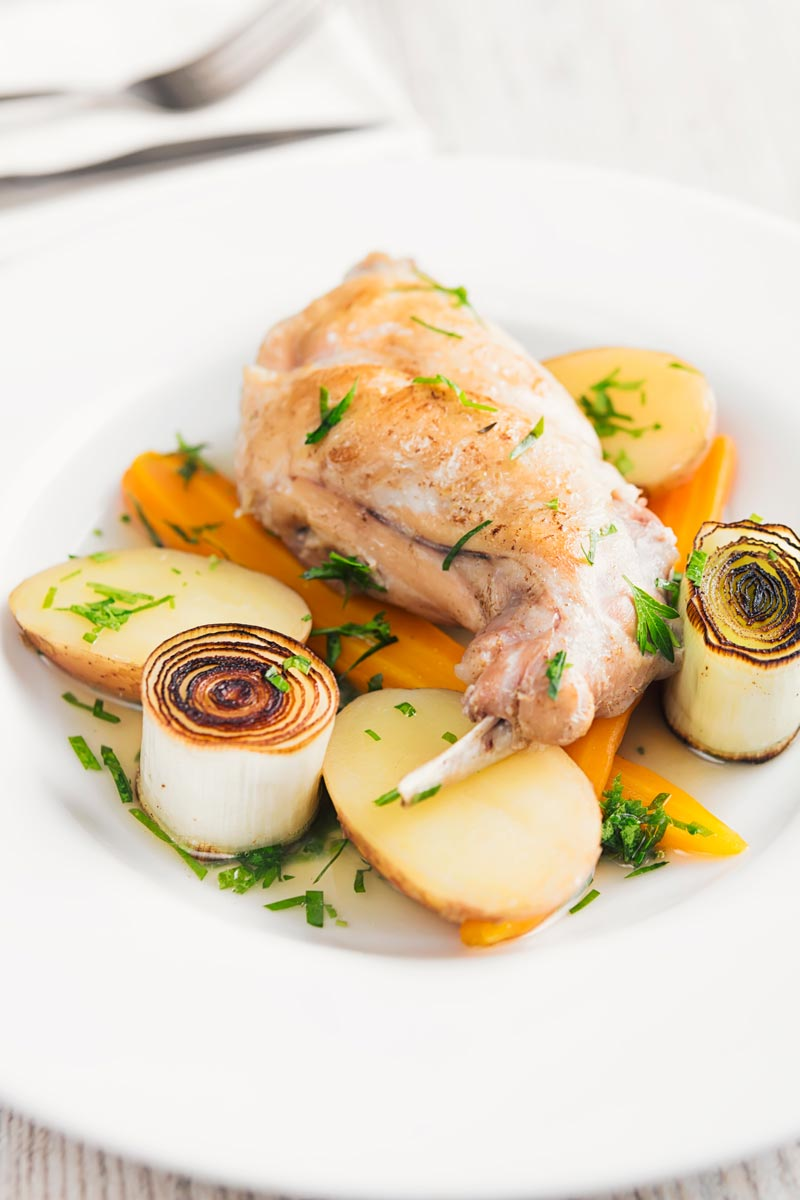 Portrait image of a braised rabbit leg served with new potatoes, carrots and seared leeks