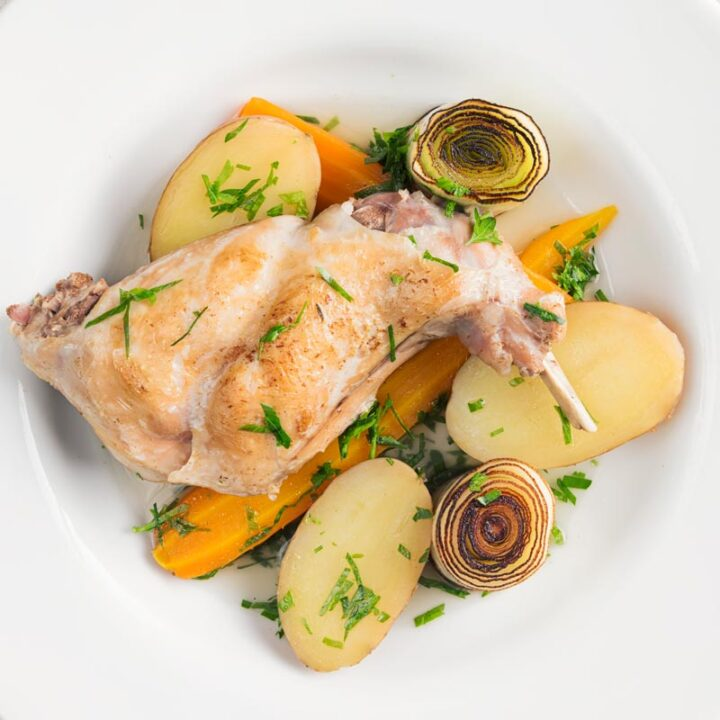 Square over head image of a braised rabbit leg served with new potatoes, carrots and seared leeks