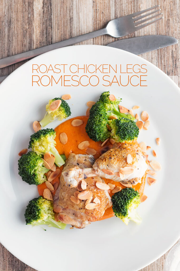 Portrait overhead image of roast chicken legs served on a romesco sauce with steamed broccoli with text