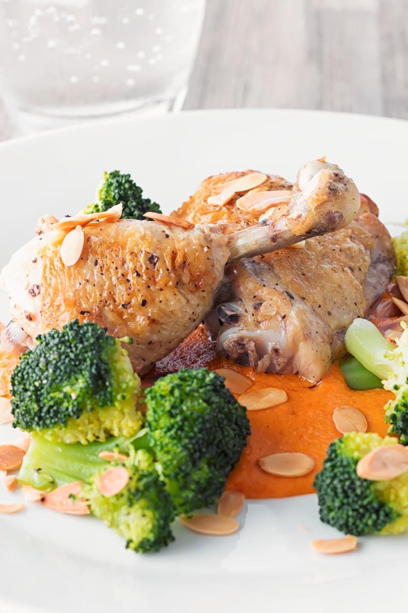 Portrait close up image of roast chicken legs served on a romesco sauce with steamed broccoli