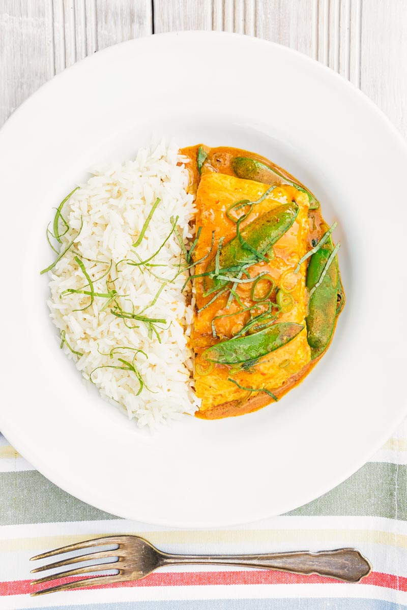 Portrait overhead image of a Thai salmon curry served with rice, shredded Thai Basil and mangetout in a white bowl