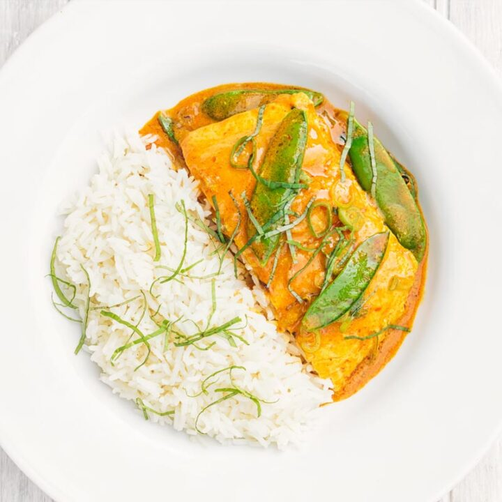 Square overhead image of a Thai salmon curry served with rice and mangetout in a white bowl