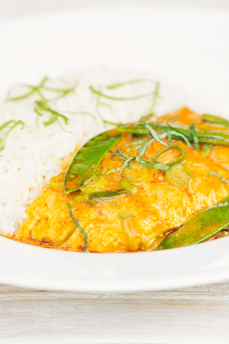 Portrait image of a Thai salmon curry served with rice and mangetout in a white bowl