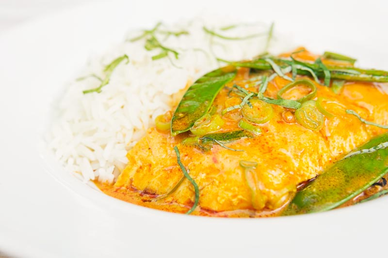 Landscape image of a Thai salmon curry served with rice, shredded Thai Basil and mangetout in a white bowl