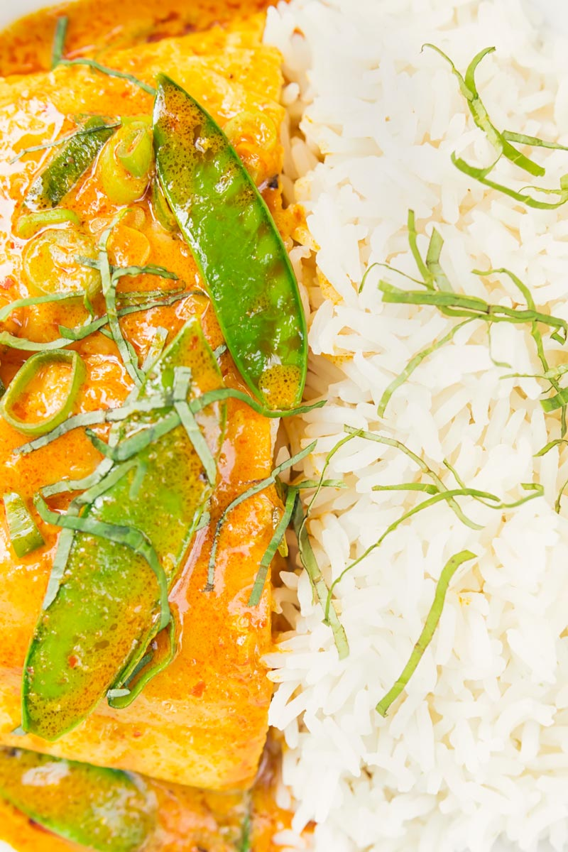 Portrait overhead closeup image of a Thai salmon curry served with rice, shredded Thai Basil and mangetout and shredded Thai basil