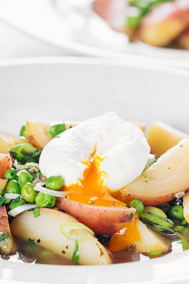 Portrait image of a new potato soup with peas in a broth topped with a perfectly poached egg