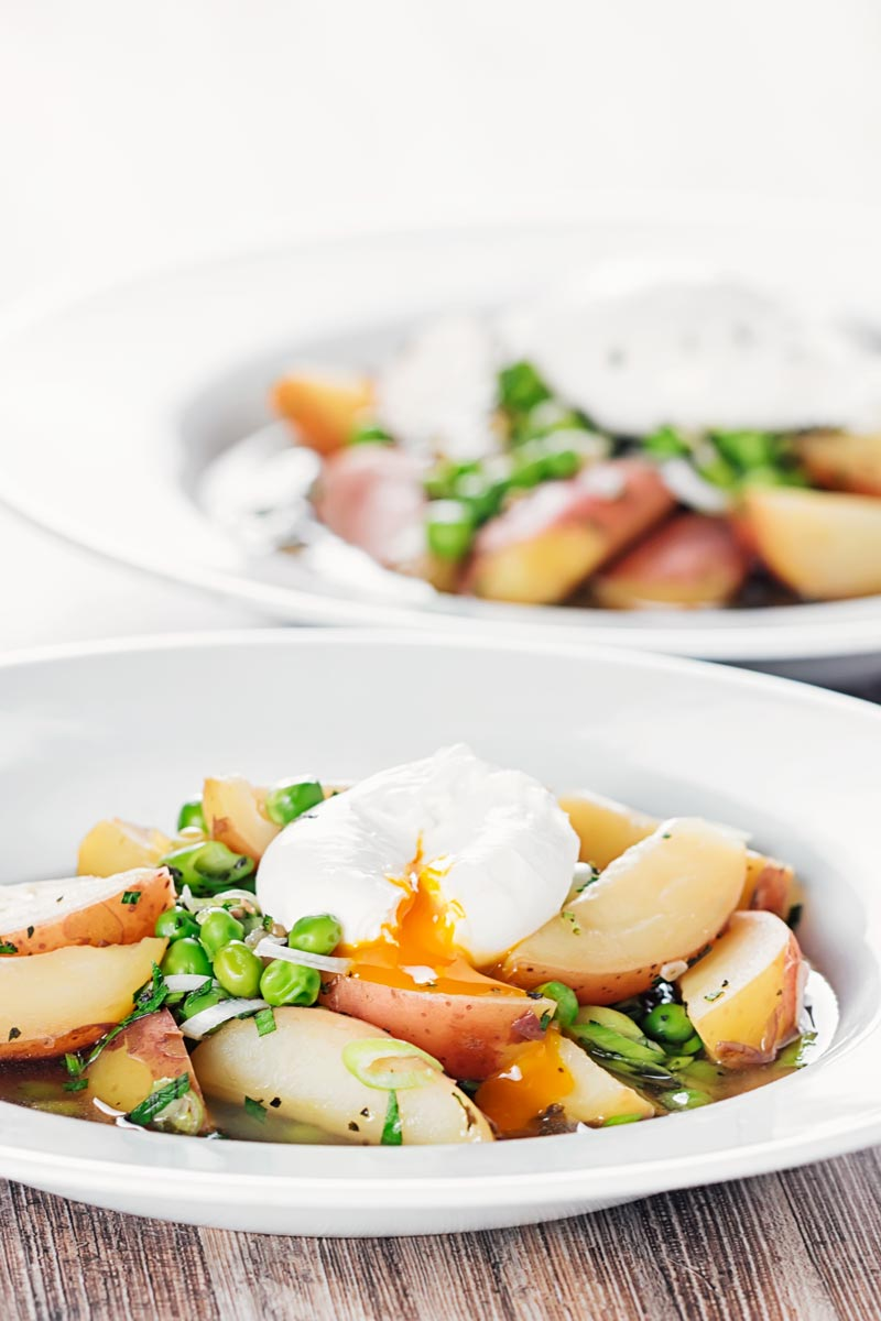 Portrait image of two bowls of new potato soup with peas in a broth topped with a perfectly poached egg