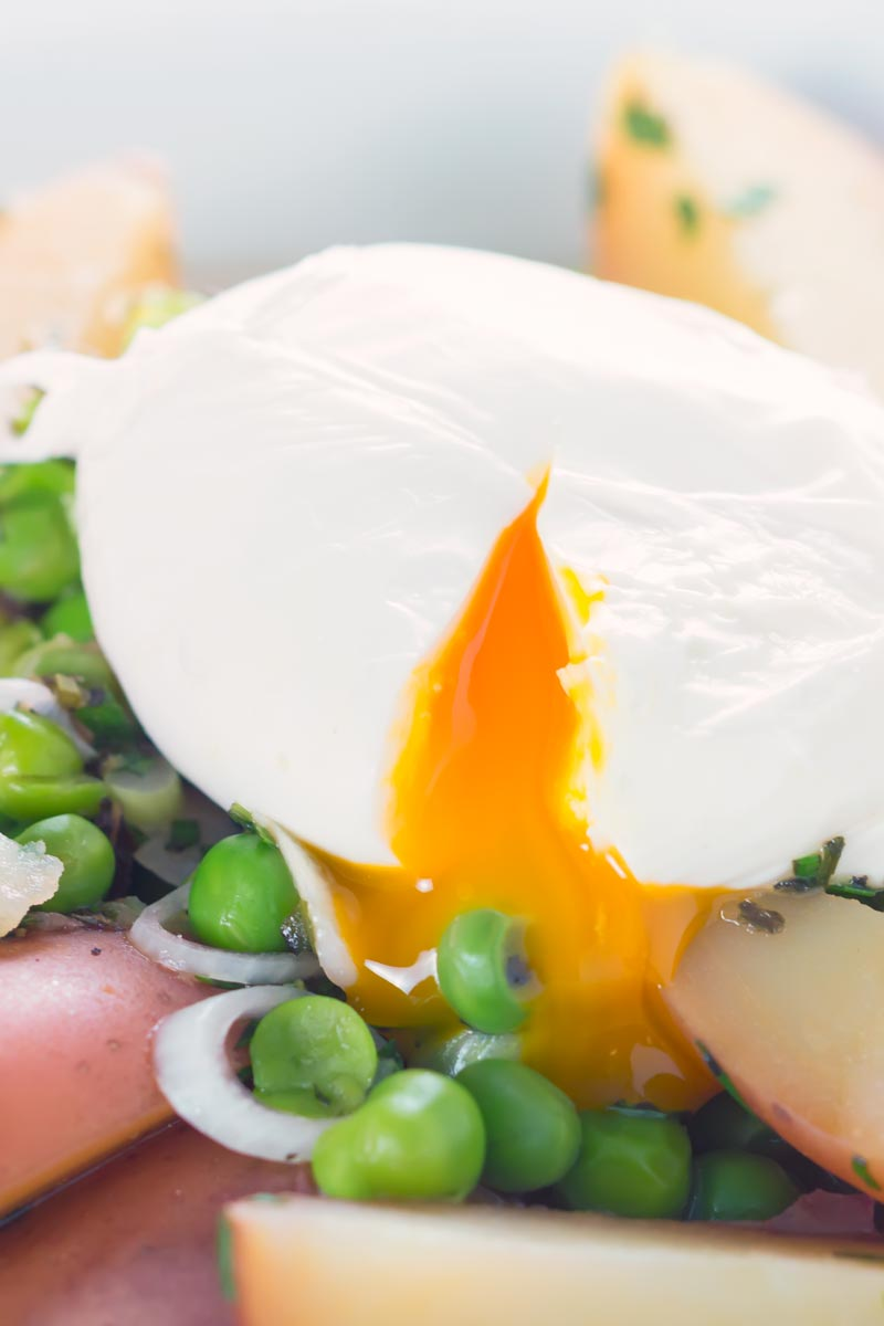 Close up portrait image of a perfect poached egg with new potatoes and peas