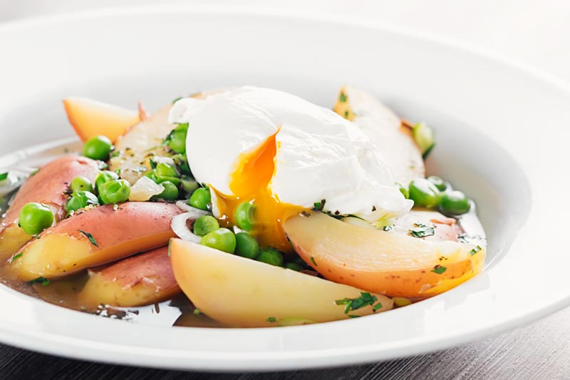 Landscape image of a new potato soup with peas in a broth topped with a perfectly poached egg