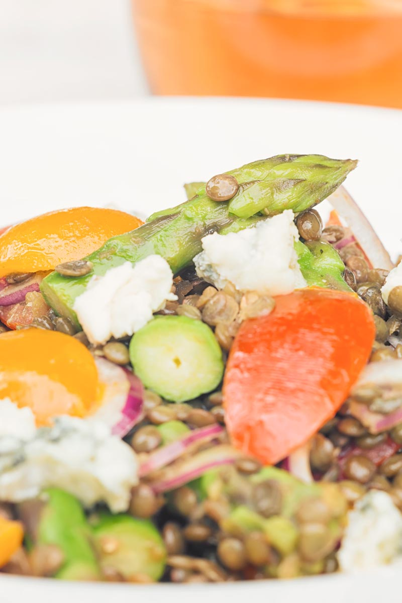 Portrait image of an asparagus spear in an asparagus salad featuring tomatoes and lentils and crumbled Roquefort cheese