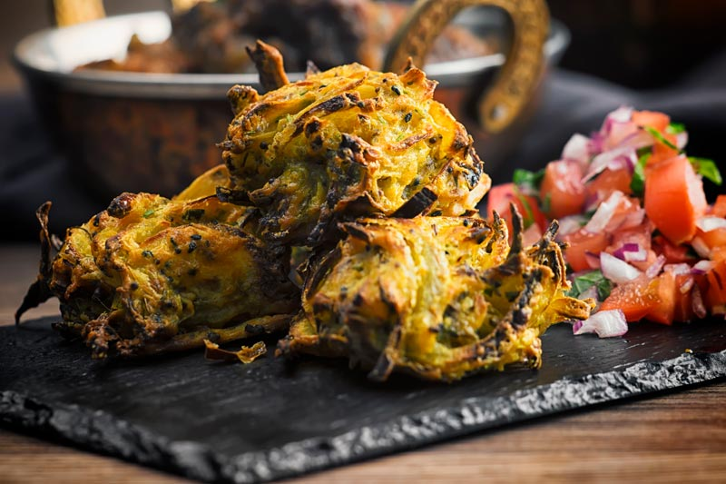 Landscape image of onion bhaji pakora served with a tomato salad on a slate