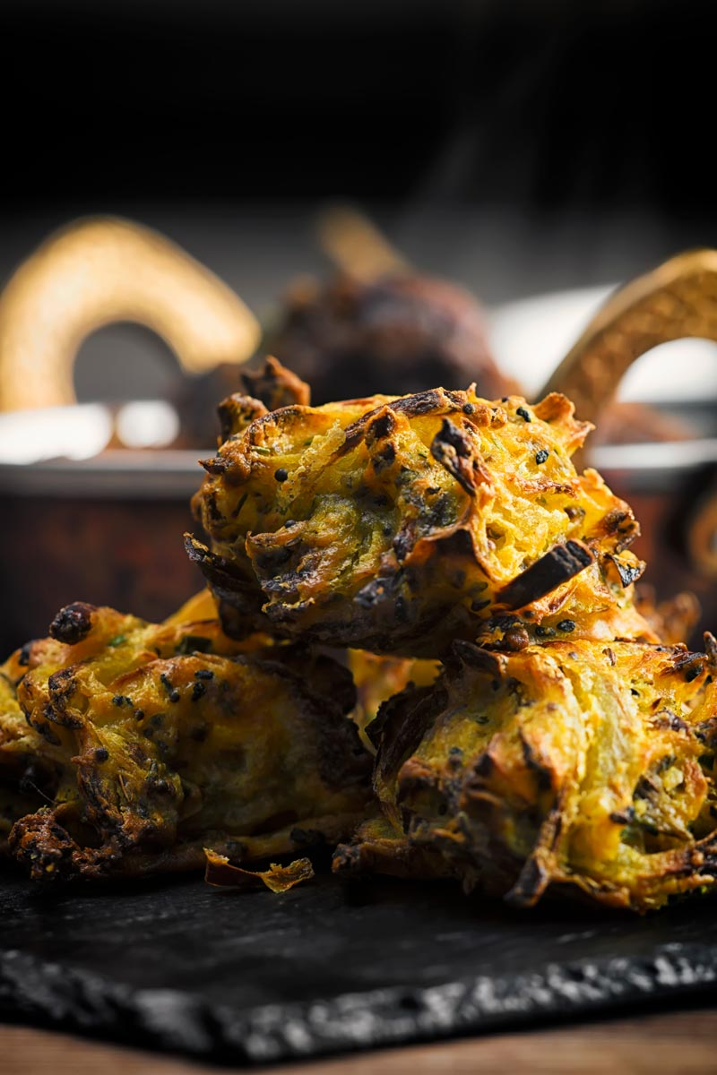 Portrait image of onion bhaji pakora served on a slate with a curry in the background