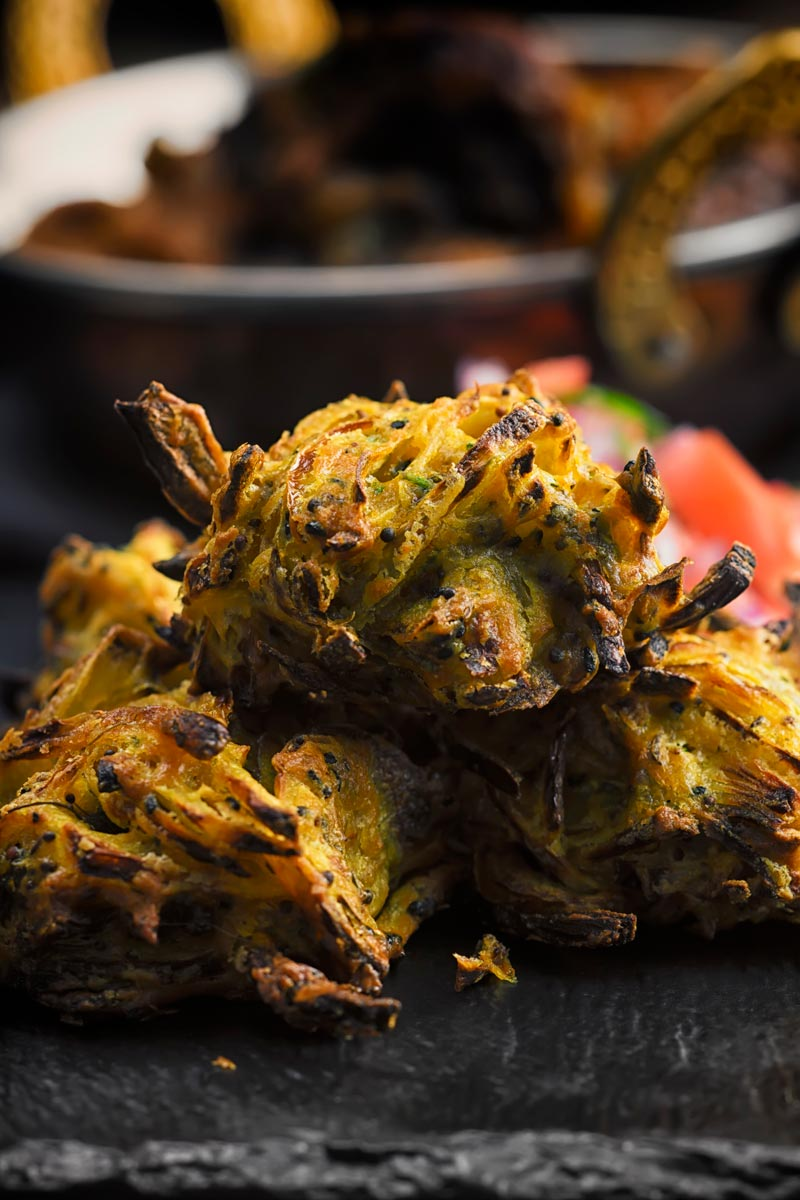 Portrait close up image of onion bhaji pakora served on a slate with a tomato salad and a curry in the background
