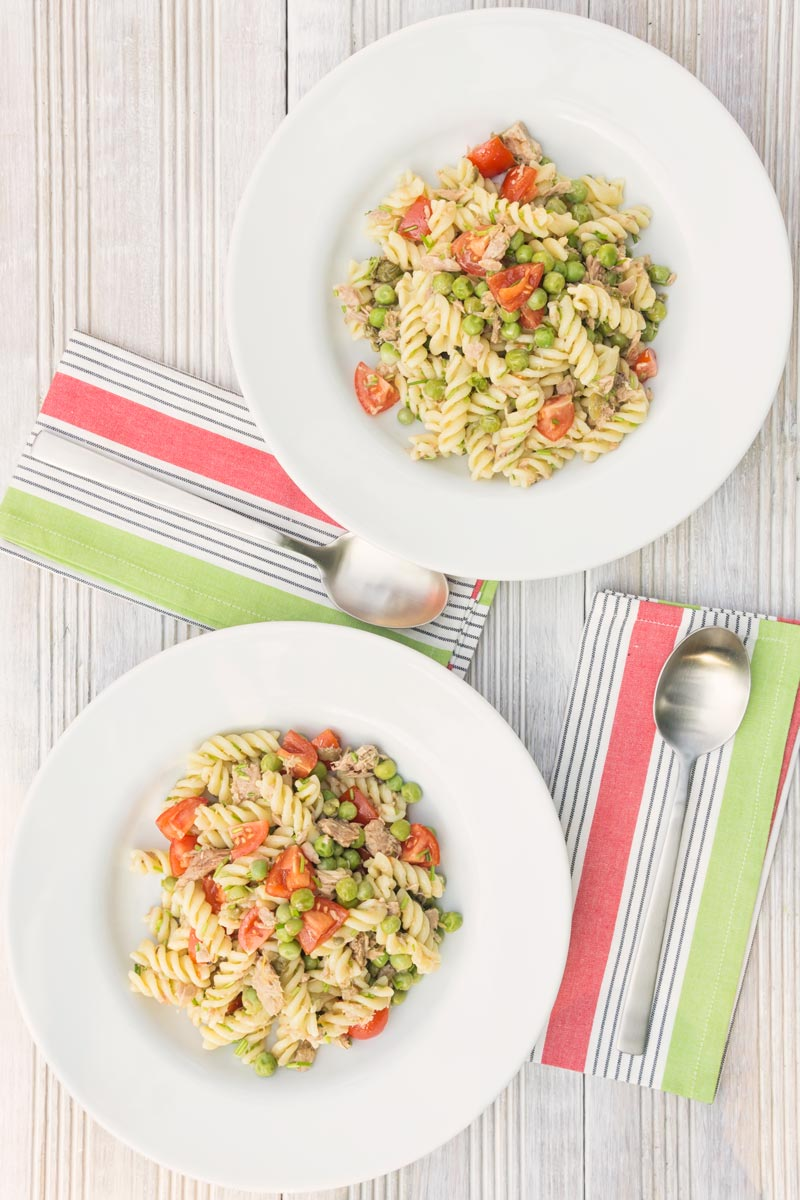 Portrait overhead image of a tuna pasta salad using fusilli pasta with cherry tomatoes and garden peas served in two white bowls