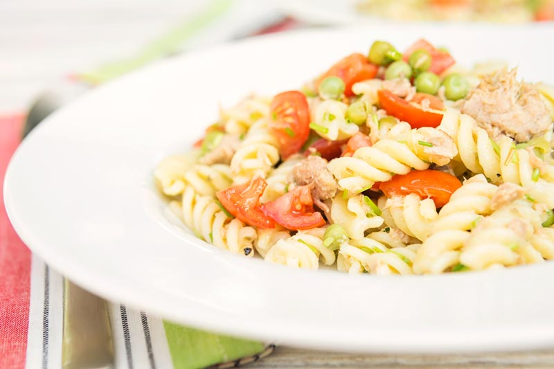 Landscape image of a tuna pasta salad using fusilli pasta with cherry tomatoes and garden peas served in a white bowl