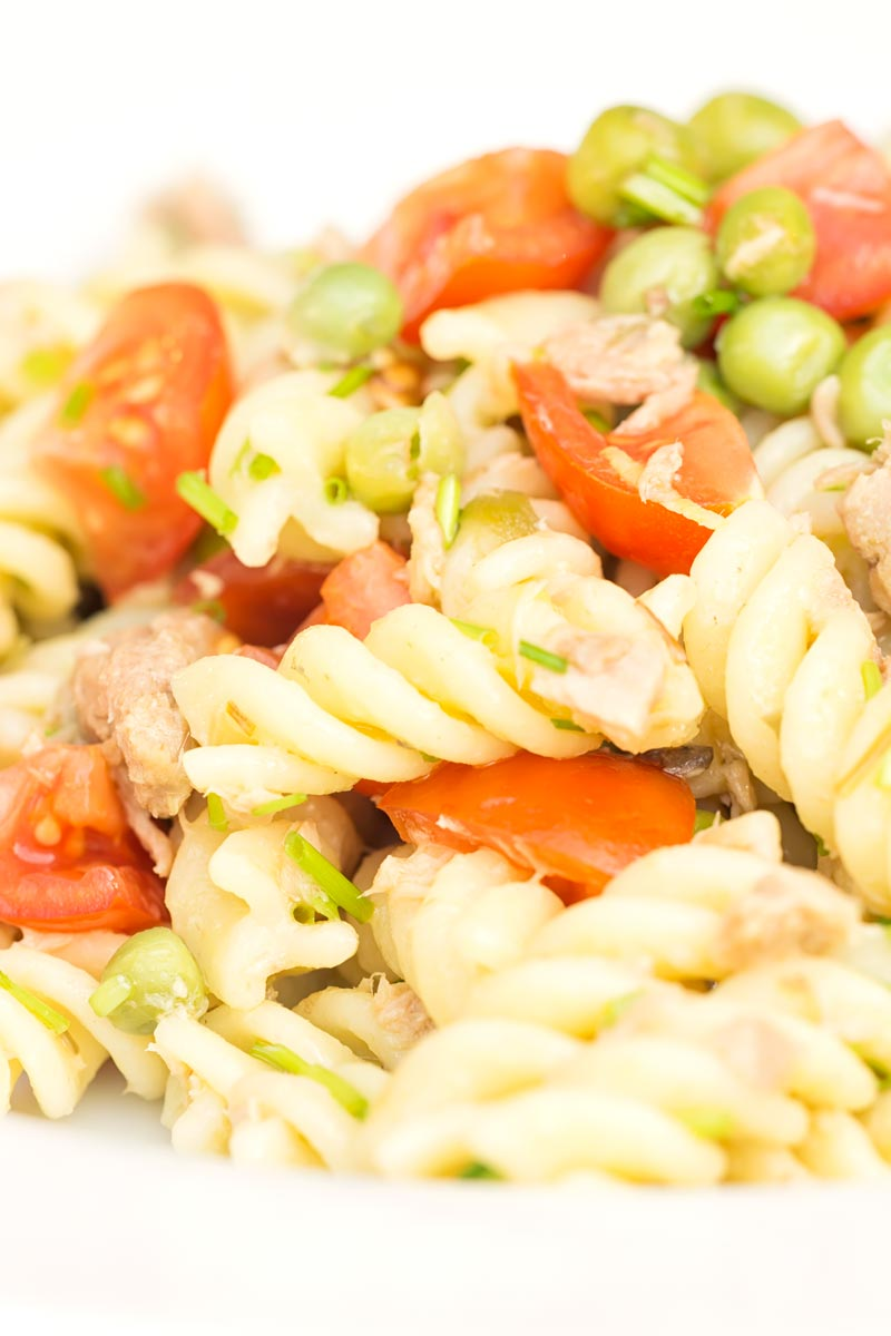 Portrait close up image of a tuna pasta salad using fusilli pasta with cherry tomatoes and garden peas served in a white bowl