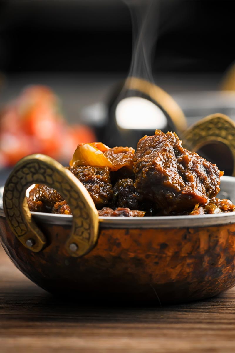 Portrait image of a steaming pork vindaloo curry served in a copper curry bowl