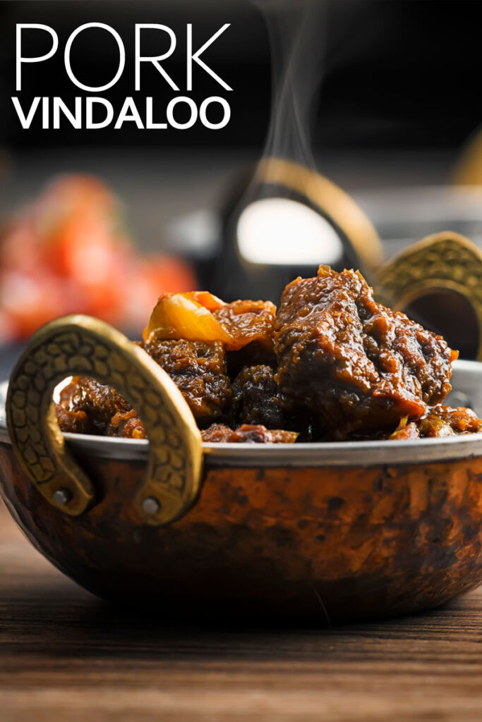 Portrait image of a steaming pork vindaloo curry served in a copper curry bowl with text