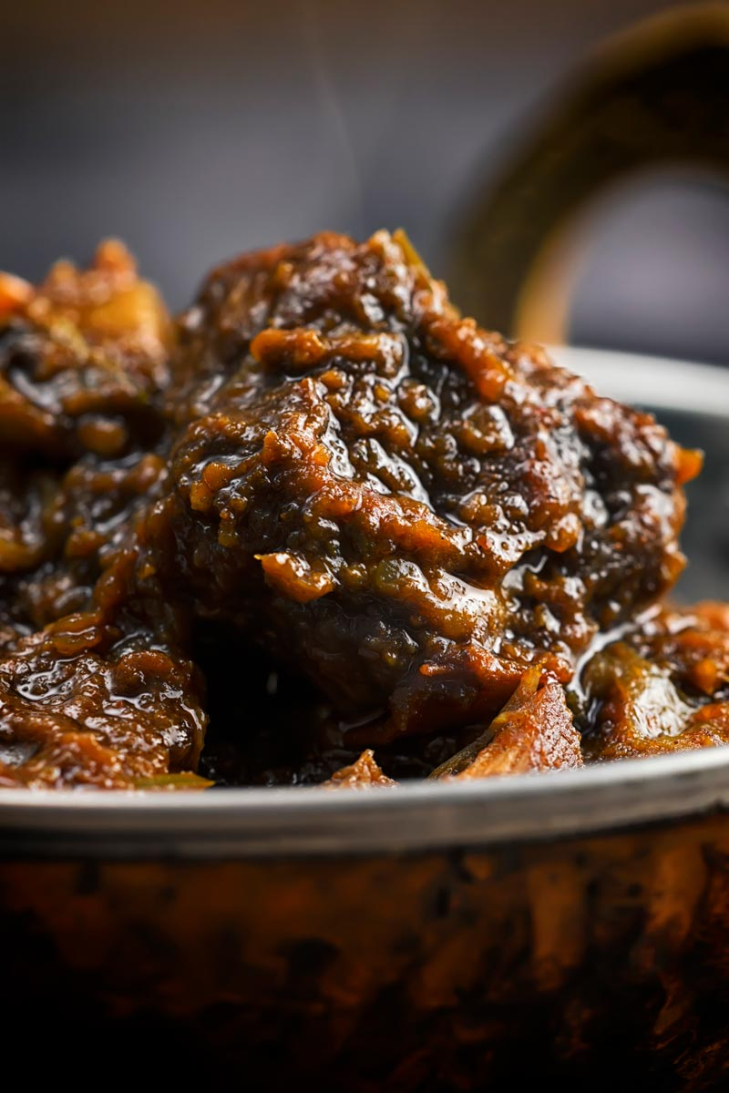 Close up portrait image of a pork vindaloo curry served in a copper curry bowl