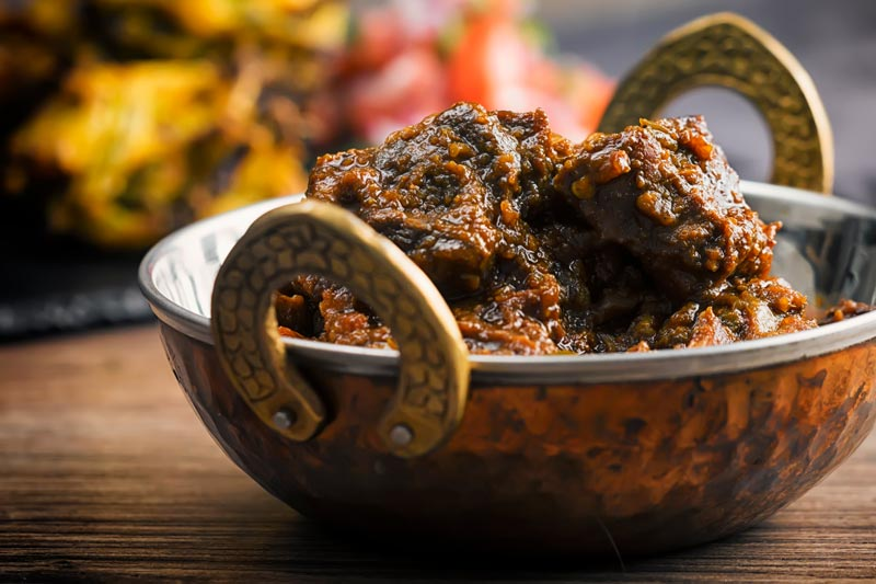 Landscape image of a pork vindaloo curry served in a copper curry bowl