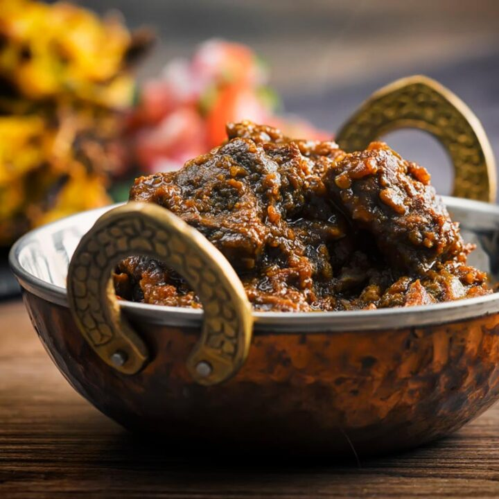 Square image of a pork vindaloo curry served in a copper curry bowl