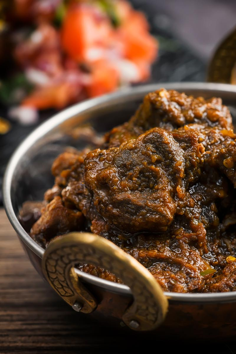Portrait image of a pork vindaloo curry served in a copper curry bowl