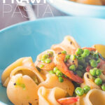 Close up portrait image of two steaming bowls of pea and prawn pasta served in a blue bowl with text overlay