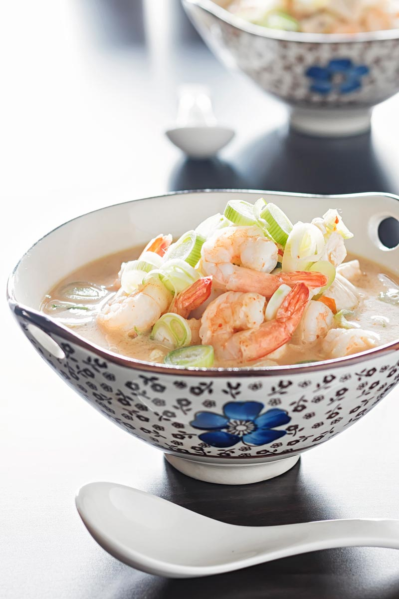 Portrait image of a chicken and prawn soup served in an Asian style bowl decorated with a blue flower
