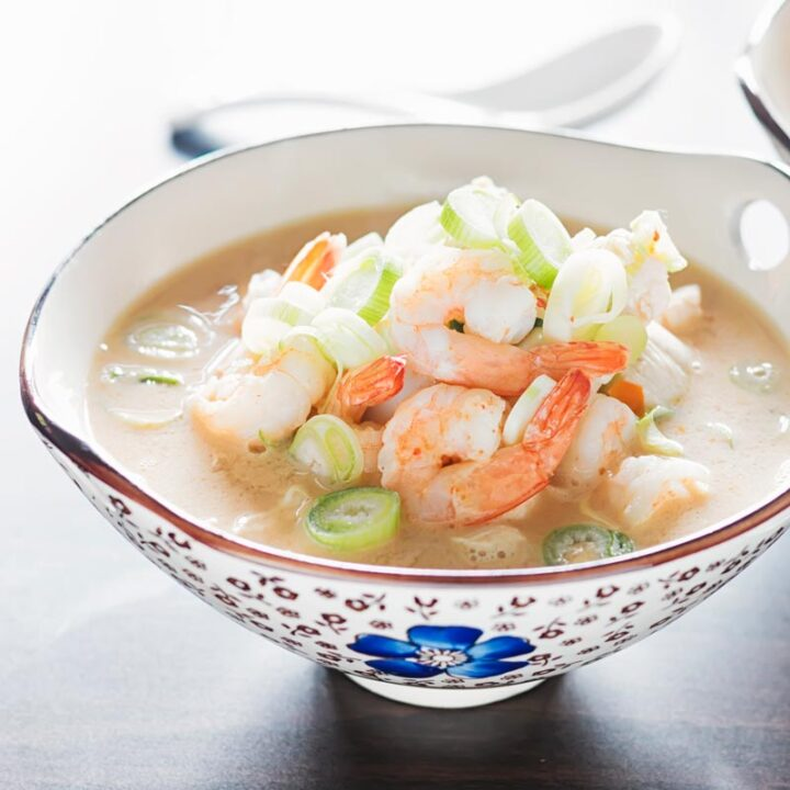 Square image of a chicken and prawn soup served in an Asian style bowl decorated with a blue flower
