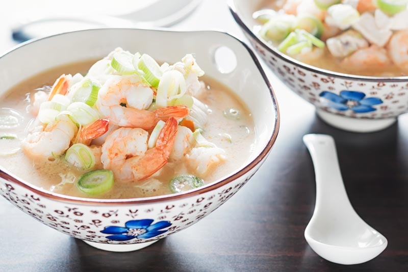 Landscape image of a chicken and prawn soup served in an Asian style bowl decorated with a blue flower