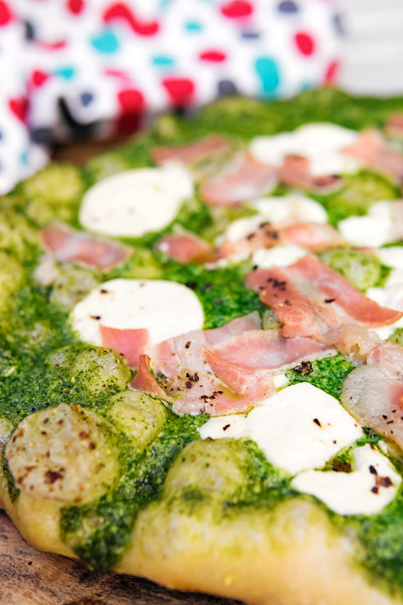 Portrait close up image of a Rocket Pesto Pizza with goats cheese and bacon
