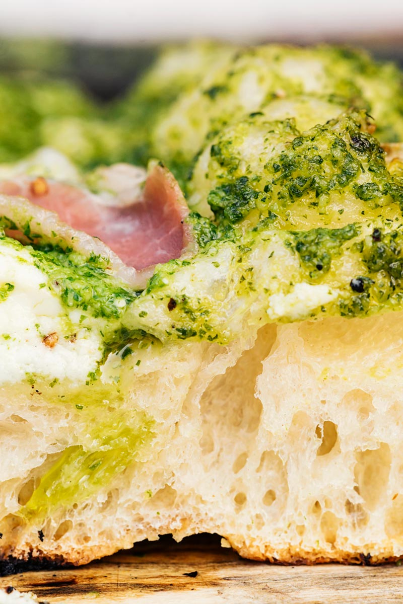 Portrait close up image of the crust of a Rocket Pesto Pizza