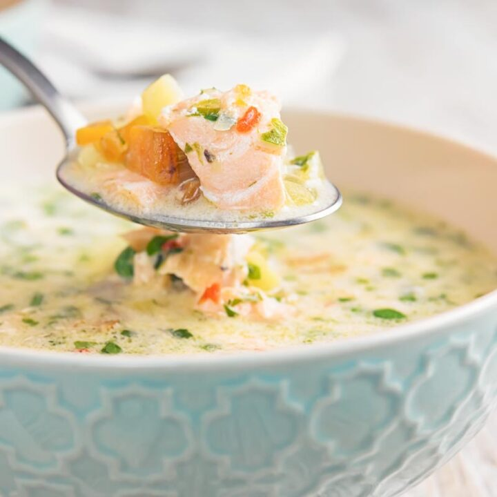 Square image of a salmon chowder served in a blue bowl with a spoonful being removed