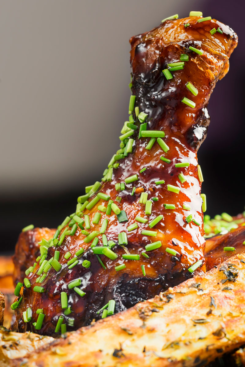 Portrait close up image of a sticky chicken drumstick with snipped chives