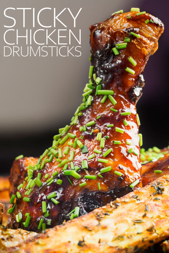 Portrait close up image of a sticky chicken drumstick with snipped chives with text